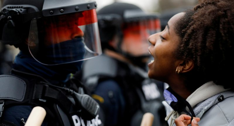 A demonstrator confronts police during a protest after police allegedly shot and killed a man, who local media report is identified by the victim's mother as Daunte Wright, in Brooklyn Center, Minnesota, U.S., April 11, 2021.