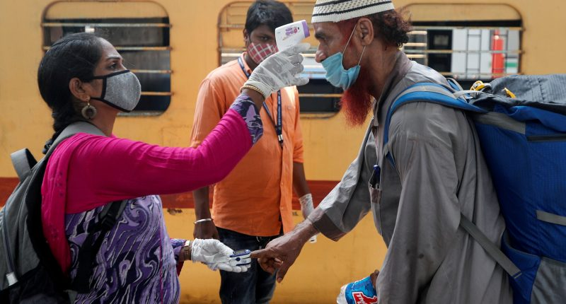 A health worker checks a passenger's temperature and pulse at a railway station platform amidst the spread of the coronavirus disease (COVID-19) in Mumbai, India, April 7, 2021.